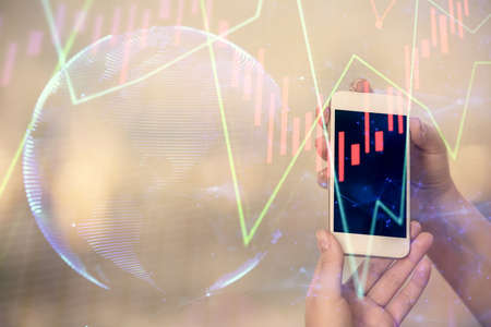 Double exposure of forex chart sketch hologram and woman holding and using a mobile device. Stock market concept. Stok Fotoğraf