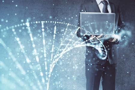 DNA hologram with businessman working on computer on background. Concept of bioengineering. Double exposure. Foto de archivo