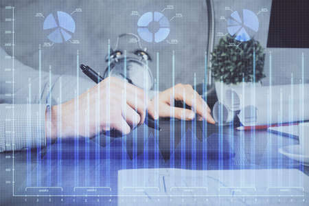 Double exposure of mans hands holding and using a phone and financial graph drawing. Analysis concept.