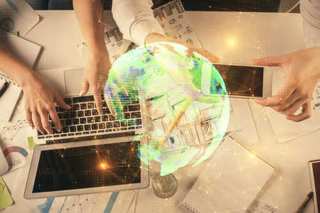 Double exposure of man and woman working together and social network theme hologram drawing. Computer background. connecting concept. Top View.