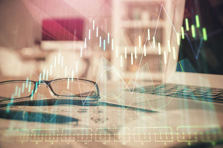 Financial chart hologram with glasses on the table background. Concept of business. Double exposure.