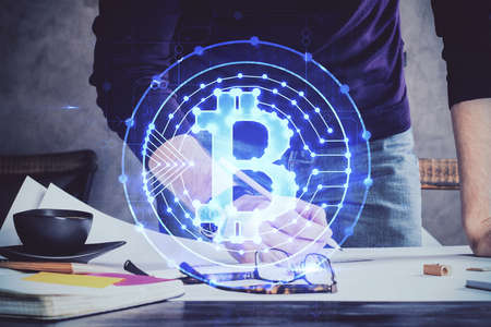 Man's hands working with notes background. Cryptocurrency and finance concept. Double exposure.