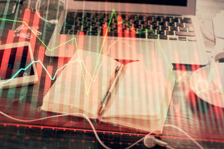 Multi exposure of financial graph drawings and desk with open notebook background. Concept of forex