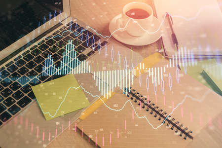 Multi exposure of forex graph drawing and desktop with coffee and items on table background. Concept of financial market trading 版權商用圖片