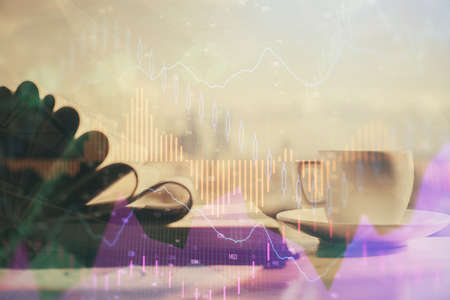 Double exposure of financial chart drawing and desktop with coffee and items on table background. Concept of forex market trading 版權商用圖片