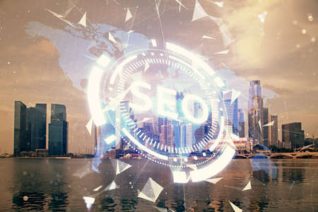 SEO hologram on city view with skyscrapers background double exposure. Search optimization concept.