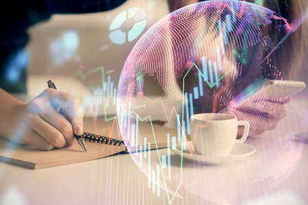 Double exposure of forex graph sketch hologram and woman holding and using a mobile device. Stock market concept.