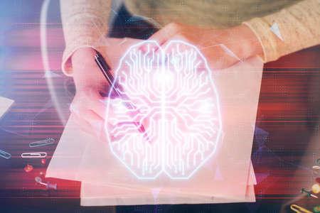 Double exposure of writing hand on background with brain hologram. Concept of learning. Foto de archivo