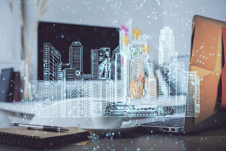 Desktop computer background in office and big town buildings hologram drawing. Double exposure. Smart city concept. 免版税图像