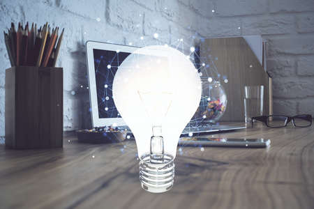 Computer on desktop in office with bulb icon hologram. Double exposure. Concept of idea. 免版税图像