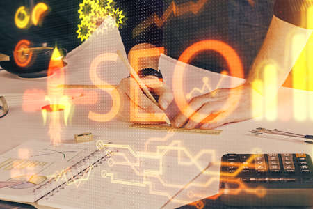 Mans hands with seo theme double exposure icon. Concept of search optimization.