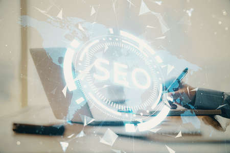Double exposure of seo icon with man working on computer on background. Concept of search engine optimization. 스톡 콘텐츠