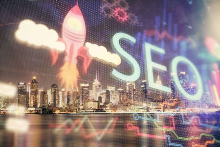 SEO hologram on city view with skyscrapers background double exposure. Search optimization concept. 스톡 콘텐츠