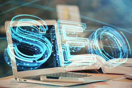 Double exposure of table with computer and seo drawing hologram. Search optimization concept.