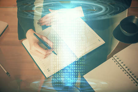 Double exposure of writing hands on background with data solution hologram on front. Technology concept. TOP view. Foto de archivo