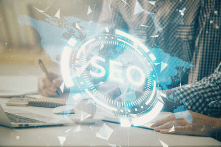 Double exposure of seo icon with man working on computer on background. Concept of search engine optimization. Foto de archivo