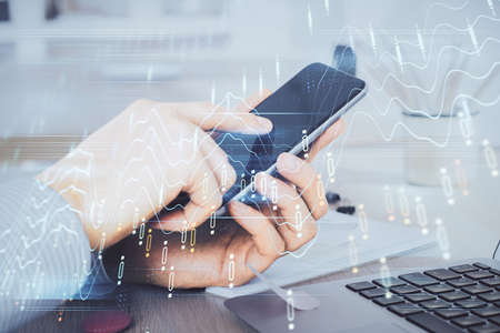 Double exposure of man's hands holding and using a digital device and forex graph drawing. Financial market concept. Reklamní fotografie