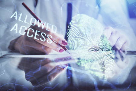 Blue fingerprint hologram over woman's hands taking notes background. Concept of protection. Double exposure 스톡 콘텐츠