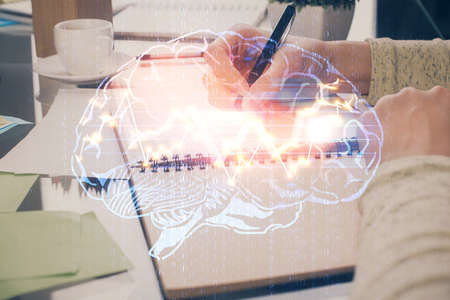 Double exposure of writing hand on background with brain hologram. Concept of learning. 스톡 콘텐츠