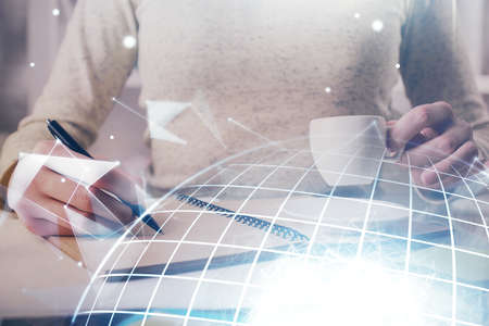 Double exposure of hands making notes with world map hologram and data theme icons. Concept of global computer data.