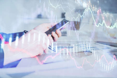 Double exposure of man's hands holding and using a phone and financial graph drawing. Analysis concept.