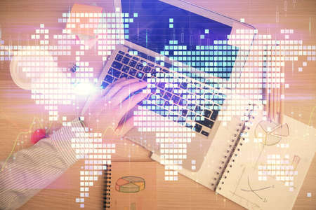 Double exposure of man's hands typing over computer keyboard and business theme hologram drawing. Top view. Financial markets concept.