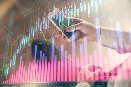 Double exposure of man's hands holding and using a digital device and forex graph drawing. Financial market concept.