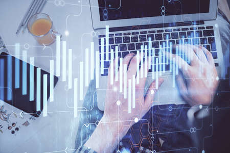 Double exposure of man's hands typing over laptop keyboard and forex chart hologram drawing. Top view. Financial markets concept. Imagens