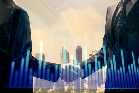 Double exposure of forex graph hologram and handshake of two men. Stock market concept.