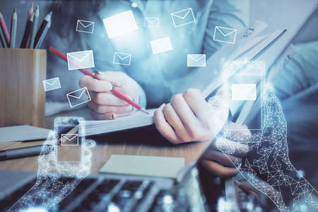 E-mail envelop theme hologram over hands taking notes background. Concept of electronic mail. Double exposure