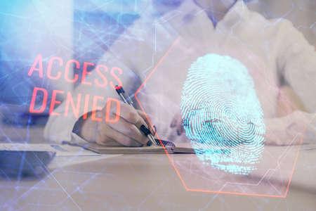 Blue fingerprint hologram over hands taking notes background. Concept of security. Double exposure Banque d'images