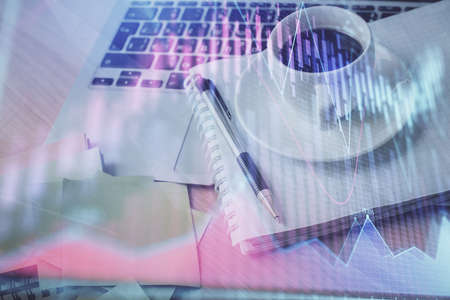 Double exposure of forex chart drawing and desktop with coffee and items on table background. Concept of financial market trading