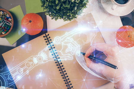 Tech theme hologram over womans hands taking notes background. Concept of hightech. Double exposure 스톡 콘텐츠