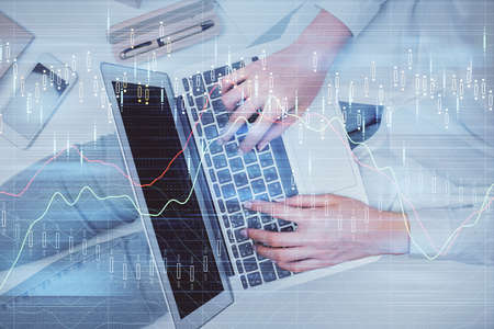 Double exposure of woman hands working on computer and forex graph hologram drawing. Top View. Financial analysis concept. 스톡 콘텐츠
