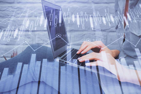 Multi exposure of woman hands typing on computer and forex chart hologram drawing. Stock market analysis concept.