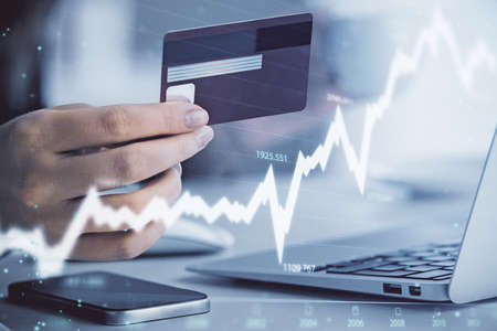 Multi exposure of woman on-line shopping holding a credit card and financial graph drawing. Stock market E-commerce concept.