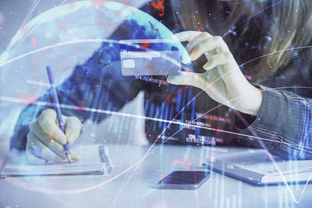 Double exposure of woman on-line shopping holding a credit card and financial graph drawing. Stock market E-commerce concept. Фото со стока