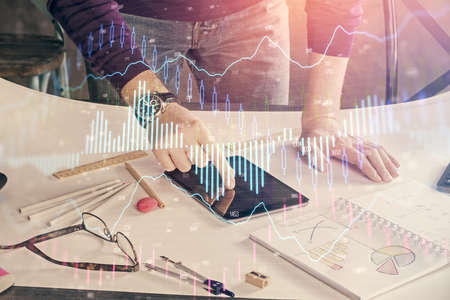 Double exposure of man's hands holding and using a digital device and forex graph drawing. Financial market concept. 免版税图像 - 157226955