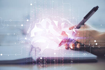 Double exposure of writing hand on background with brain hologram. Concept of learning. 写真素材
