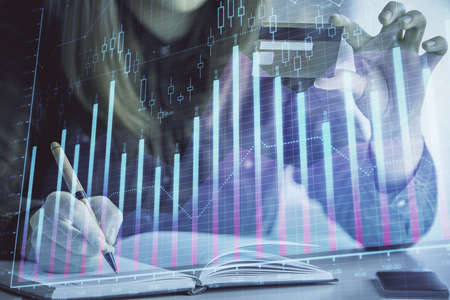 Double exposure of woman on-line shopping holding a credit card and financial graph drawing. Stock market E-commerce concept. Stock fotó