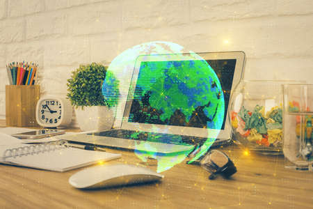 Computer on desktop with social network hologram. Multi exposure. Concept of international people connections.
