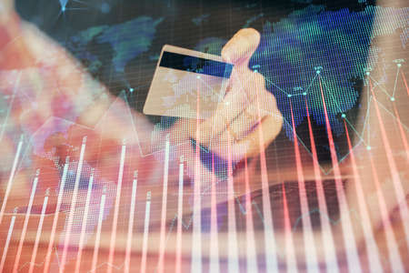 Double exposure of man hands holding a credit card and Forex graph drawing. Stock trading and digital fintech in Internet E-commerce concept. Фото со стока