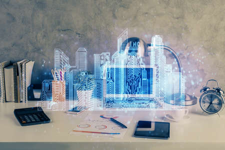 Desktop computer background in office and big town buildings hologram drawing. Double exposure. Smart city concept. Archivio Fotografico