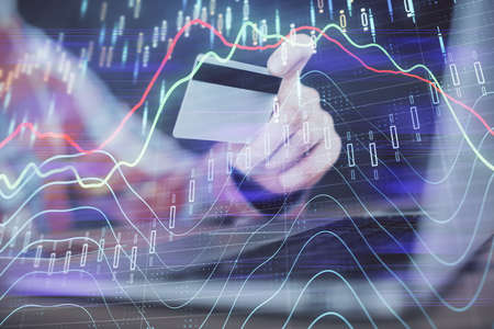 Double exposure of man hands holding a credit card and Forex graph drawing. Stock trading and digital fintech in Internet E-commerce concept. 版權商用圖片