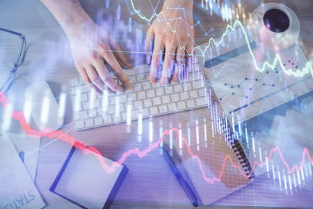 Multi exposure of mans hands typing over computer keyboard and forex graph hologram drawing. Top view. Financial markets concept.