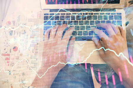 Double exposure of mans hands typing over laptop keyboard and forex chart hologram drawing. Top view. Financial markets concept.