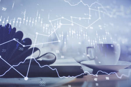 Double exposure of financial chart drawing and desktop with coffee and items on table background. Concept of forex market trading