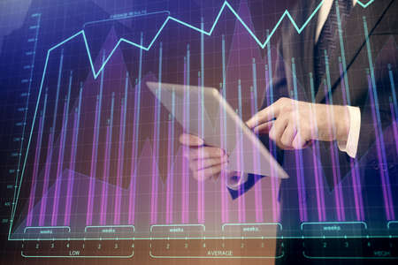 Double exposure of mans hands holding and using a digital device and forex graph drawing. Financial market concept.