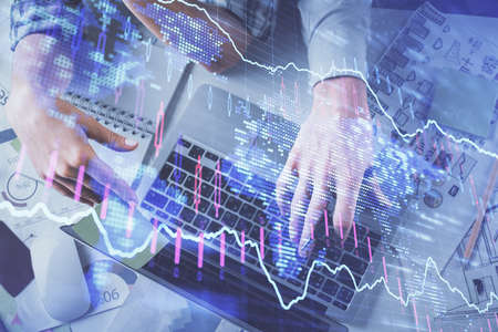 Double exposure of man and woman working together and forex graph hologram drawing. Financial analysis concept. Computer background. Top View. 免版税图像