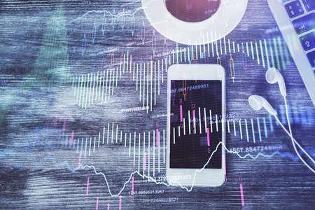 Double exposure of forex chart hologram over desktop with phone. Top view. Mobile trade platform concept. 版權商用圖片